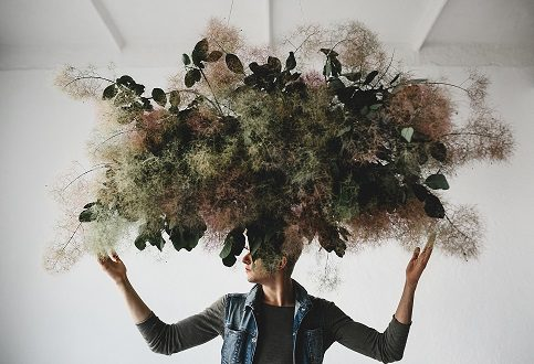 Large decorative bouquet made of green leaves and moss hangs ove